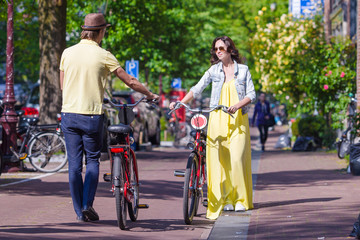 Young happy couple on bikes in old streets in Amsterdam