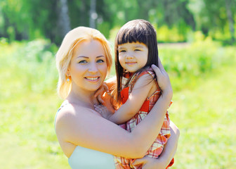 Portrait of happy smiling mother and child together outdoors in