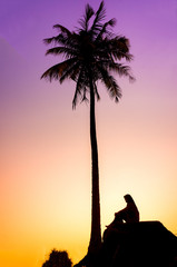 Sillouette of coconut tree and young muslim woman during sunrise