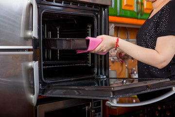 Woman holding pan  near oven