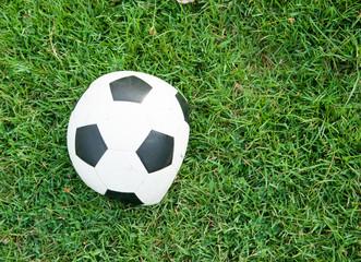 Deflated soccer ball on grass