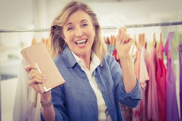 Cheering woman going shopping and showing wallet