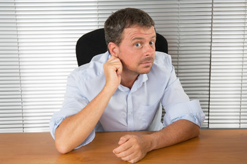 Man at work listening with hand on ear over white background