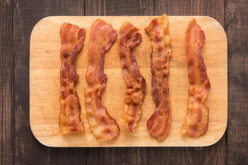 Fried bacon strips on the wooden board