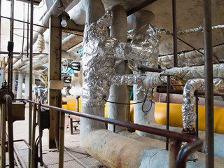 Old rusty industrial steel pipelines, valves and equipment at po