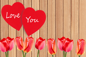 Two red heart and tulips over wooden texture