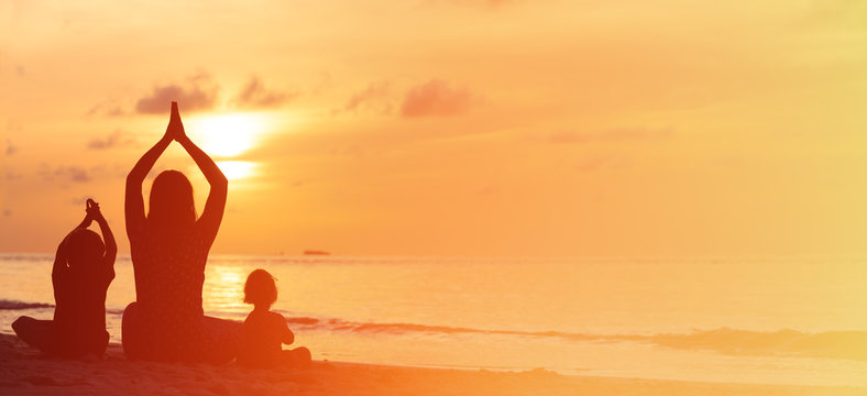 silhouette of mother and kids doing yoga at sunset sea