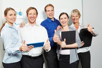 Business Team im Büro hält Daumen hoch