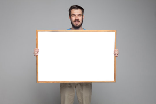 The smiling man showing empty white billboard or banner