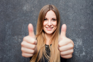 Teenage girl showing thumbs up with both hands