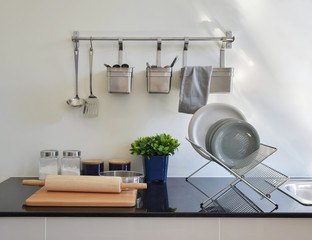 modern ceramic kitchenware and utensils on the black granite cou