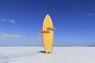 Arms hugging a yellow surfboard. Australia.