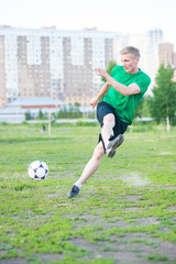 Soccer player strongly hits the ball.