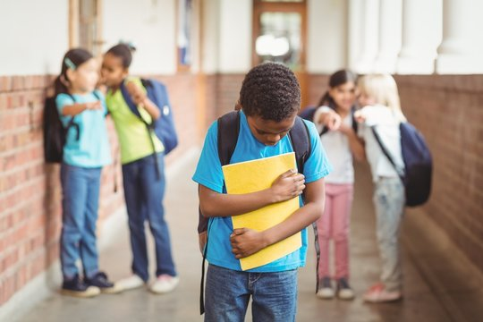 Sad pupil being bullied by classmates at corridor