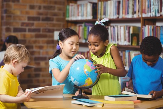 Surprised pupils studying globe in the library
