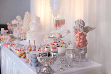 Dessert table for a party. Ombre cake, cupcakes, sweetness and f