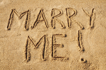 The words Marry Me written in the sand on the beach