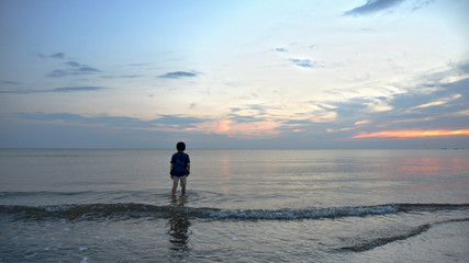夕暮れの浜辺と少年