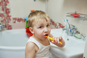 little boy learns to brush teeth