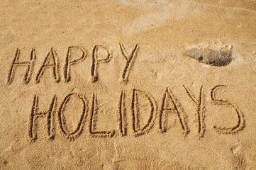 The words Happy Holidays written in the sand on the beach