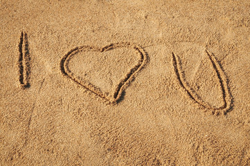 The words I Love You written in the sand on the beach