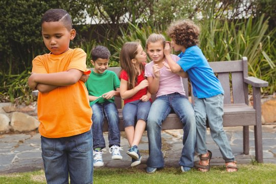 Upset child standing away from group
