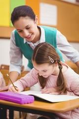 Teacher helping a little girl during class
