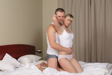 woman and her husband playing in the bed