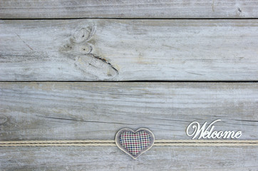 Blank rustic sign with Welcome and fabric heart with rope border