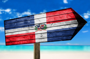 Dominican Republic Flag on wooden table sign on beach background