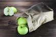 Äpfel der Sorte Delbar in einer Papiertüte auf Holzhintergrund