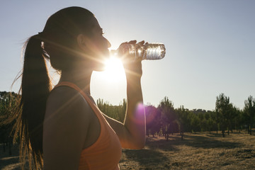 Backlighting of a runner woman drinking water
