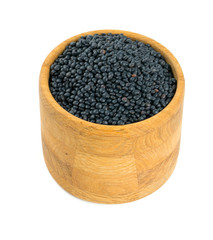black lentils in a bowl isolated on white