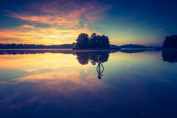 Vintage photo of beautiful sunrise over calm lake.