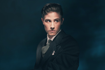 Classic stylish vintage man in suit and tie. Hair combed back.