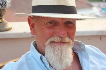 An englishman with a beard wearing a stylish hat