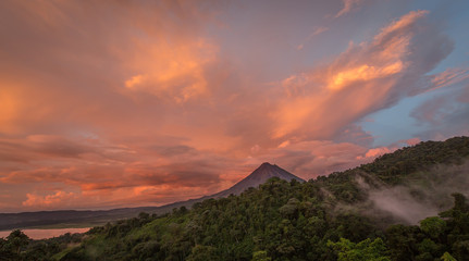 Sunset on Lake Arenal and Arenal Volcano in Costa Rica, brings Shades of red and orange as clouds rise from the jungle floor