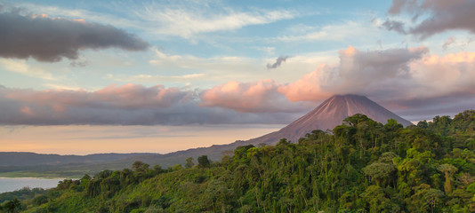 Poster Jungle Arenal Volcano at Sunrise in Costa Rica, as the sun reflects on the newly formed clouds