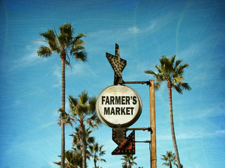 aged and worn vintage photo of farmers market sign with palm trees