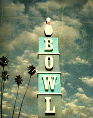 aged and worn vintage photo of bowling alley sign with palm trees