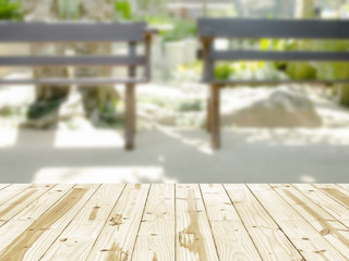 Wood table top on blurry two bench in the garden