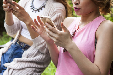 Two young women using a mobile phone in a park bench