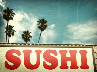 aged and worn vintage photo of sushi sign and palm trees.