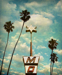 aged and worn vintage photo of neon sign and star with palm trees