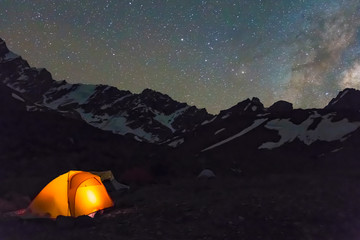 Night mountain landscape with illuminated tent.