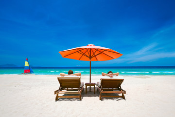 Couple on a tropical beach on deck chairs under a red umbrella.