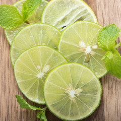 Fresh lime slices on wood background.
