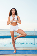 Woman standing in yoga pose on one leg