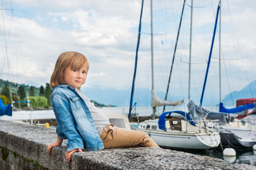 Fashion portrait of a cute little blond boy sitting by the lake, wearing denim shirt and beige trousers