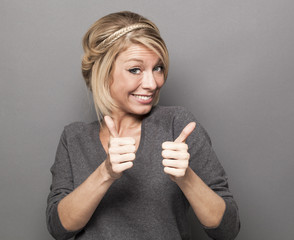 agreement concept - smiling young blonde woman giving a double thumb up for satisfaction